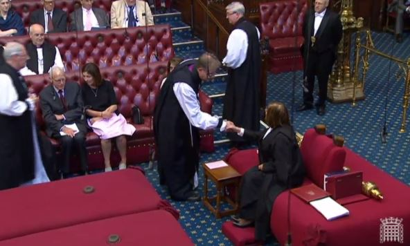 The Bishop of Oxford shakes hands with the Lord Speaker, before taking his seat on the Bishops' Benches